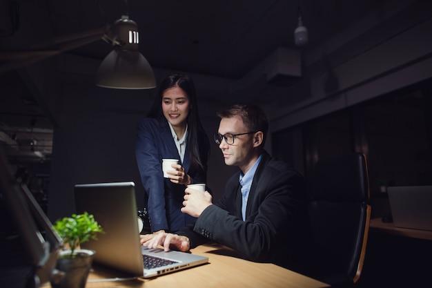 Gut aussehender mann, der spät arbeitet, sitzend auf schreibtisch mit asiatischem sekretärmädchen im büro nachts. geschäftsmann-kontrollbericht vom laptop von trinkendem kaffee der mitarbeiterfrau
