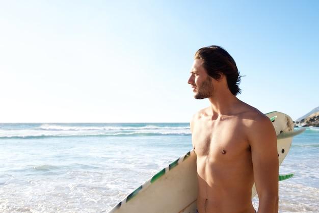 Gut aussehender mann, der surfbrett am strand hält