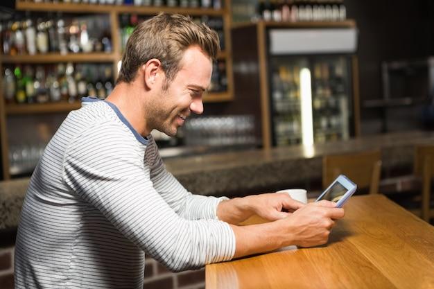 Gut aussehender mann, der tablet-computer verwendet