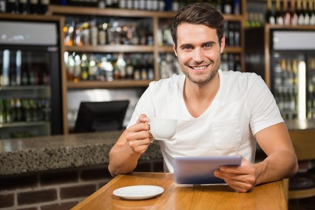 Gut aussehender mann, der tablette verwendet und kaffee trinkt