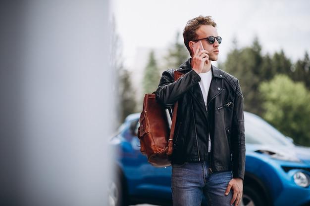 Gut aussehender mann, der telefon mit dem auto verwendet