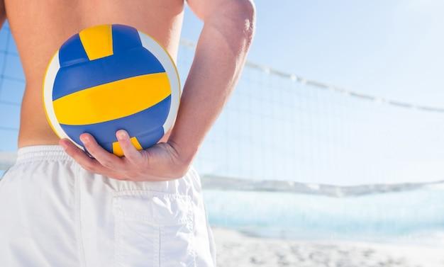 Gut aussehender mann, der volleyball hält