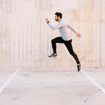 Gut aussehender mann, der während des trainings springt