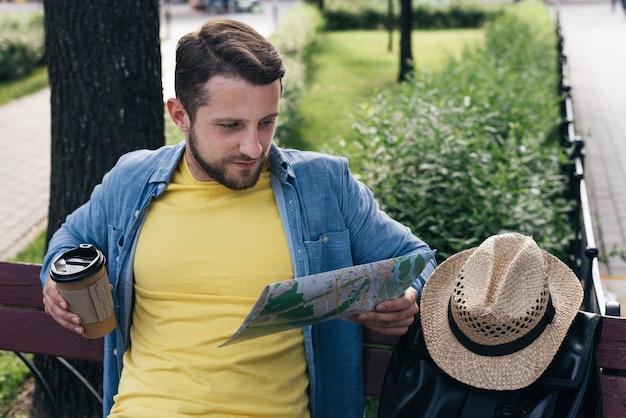 Gut aussehender mann, der wegwerfkaffeetasse beim ablesen der karte beim sitzen im park hält