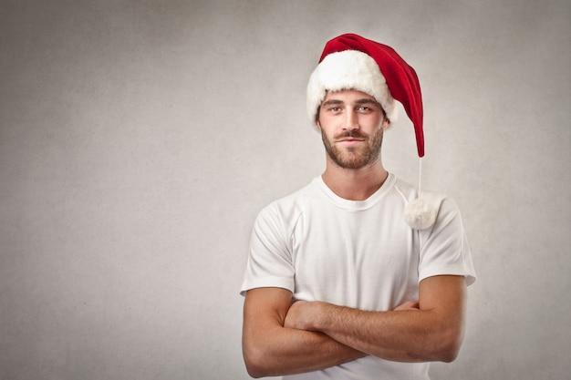 Gut aussehender mann, der weihnachtsmanns hut trägt