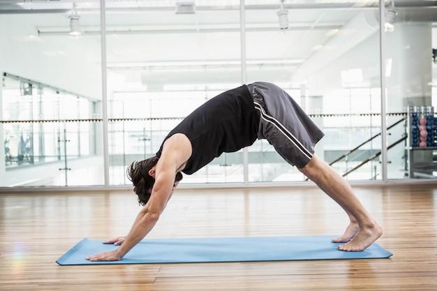 Gut aussehender mann, der yoga auf matte im studio tut
