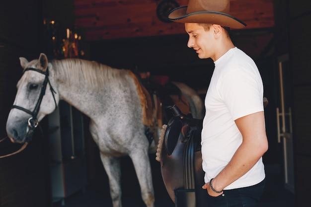 Gut aussehender mann, der zeit mit einem pferd verbringt