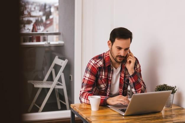 Gut aussehender mann, der zu hause an dem büro des laptops, sprechend am telefon arbeitet.