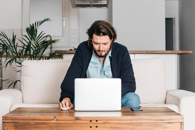 Gut aussehender mann, der zu hause auf sofa unter verwendung des laptops sitzt