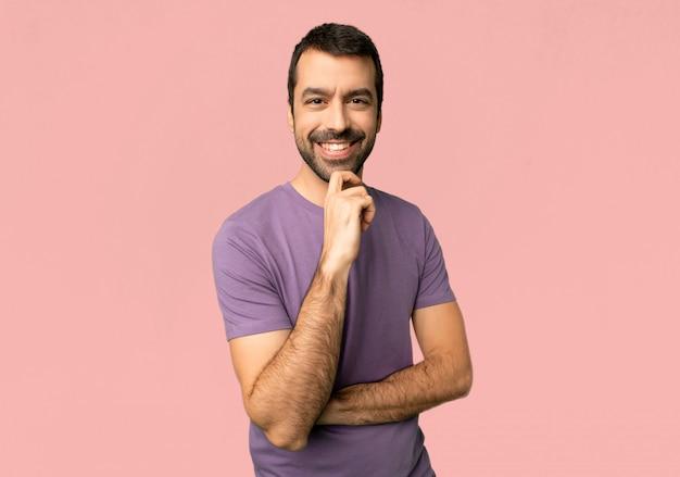 Gut aussehender mann, der zur front mit überzeugtem gesicht auf lokalisiertem rosa hintergrund lächelt und schaut