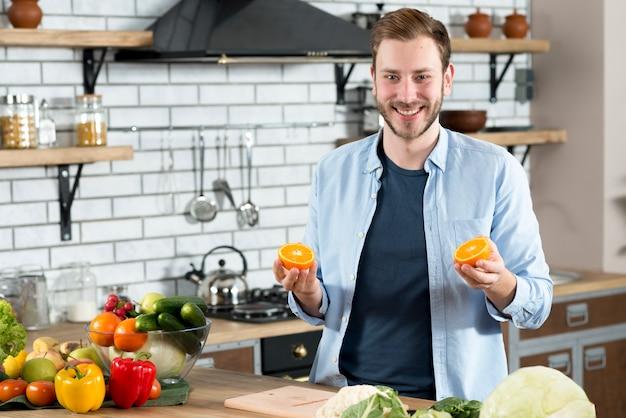 Gut aussehender mann, der zwei orangenscheiben in der küche hält