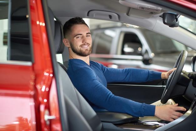 Gut aussehender mann des brunette in der blauen strickjacke lächelnd im roten auto.