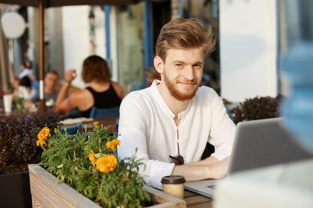 Gut aussehender mann des erwachsenen ingwers mit laptop, der auf der terrasse eines restaurants oder cafés sitzt