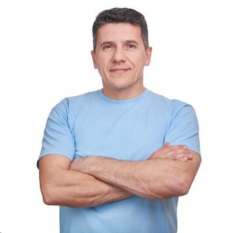 Gut aussehender mann des porträts, der blaues informelles t-shirt mit den gefalteten armen lokalisiert trägt