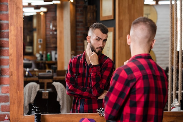 Gut aussehender mann des porträts, der seinen haarschnitt im spiegel überprüft