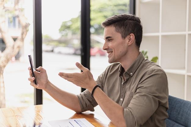 Gut aussehender mann führt einen videoanruf mit einer person auf einem smartphone. junge geschäftsleute nutzen smartphones, um mit ihren partnern von angesicht zu angesicht zu kommunizieren. konzept der verwendung von kommunikationstechnologie.