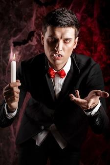 Gut aussehender mann, gekleidet in einem dracula-kostüm für halloween. attraktiver vampir mit kerzen streckt seine hand nach vorne