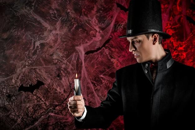 Gut aussehender mann, gekleidet in einem dracula-kostüm für halloween. attraktiver vampir mit kerzen