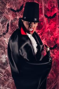 Gut aussehender mann, gekleidet in einem dracula-kostüm für halloween. attraktiver vampir