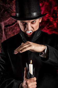 Gut aussehender mann, gekleidet in einem dracula-kostüm für halloween. schrecklicher vampir mit kerzen