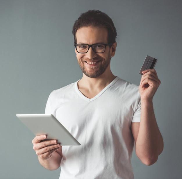 Gut aussehender mann hält eine digitale tablette und eine kreditkarte