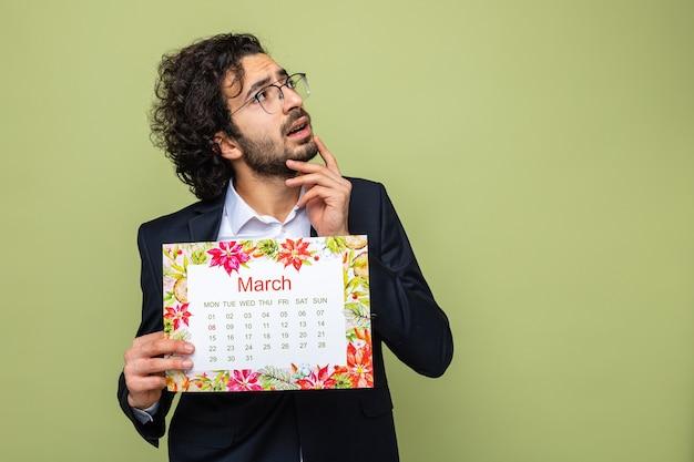 Gut aussehender mann im anzug, der einen papierkalender des monats märz hält, der verwirrt aufblickt und den internationalen frauentag am 8. märz feiert, der über grünem hintergrund steht