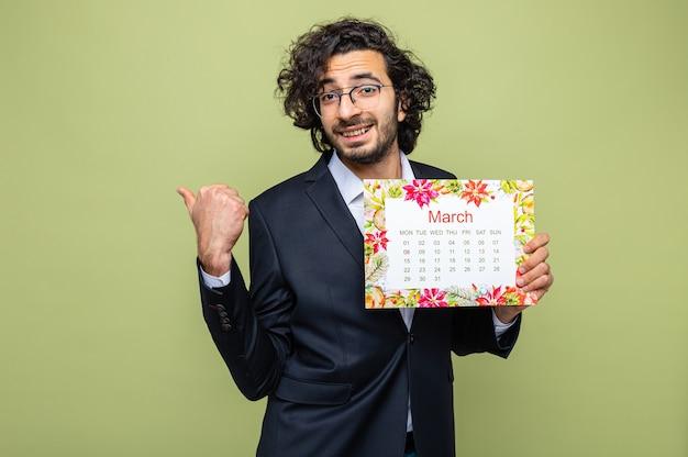 Gut aussehender mann im anzug, der einen papierkalender des monats märz hält und in die kamera schaut, die mit dem daumen nach hinten zeigt und den internationalen frauentag am 8. märz feiert, der über grünem hintergrund steht