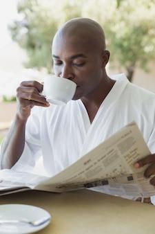 Gut aussehender mann im bademantel, der draußen kaffee trinkt