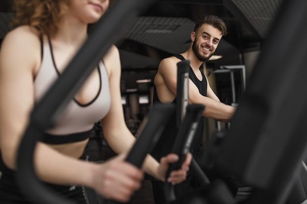 Gut aussehender mann im fitnessstudio, der übung macht