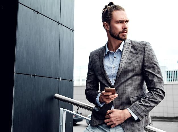 Gut aussehender mann im grauen karierten anzug mit smartphone