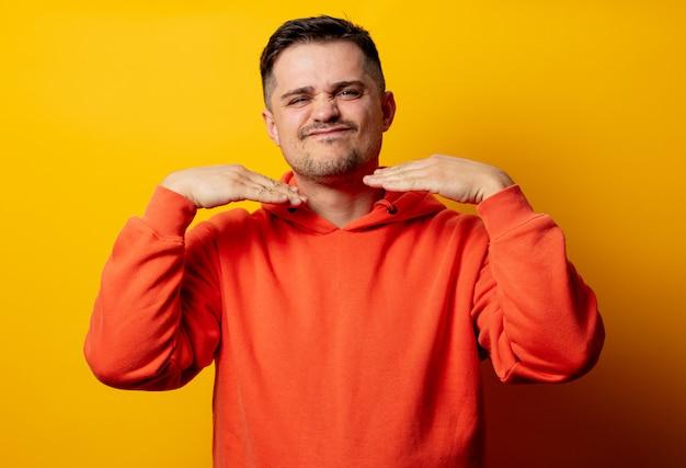 Gut aussehender mann im hoodie auf gelber wand