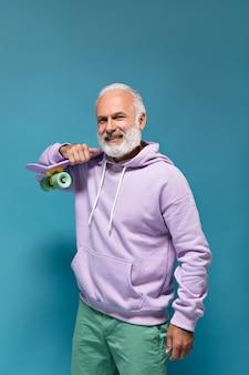 Gut aussehender mann im lila hoodie mit longboard