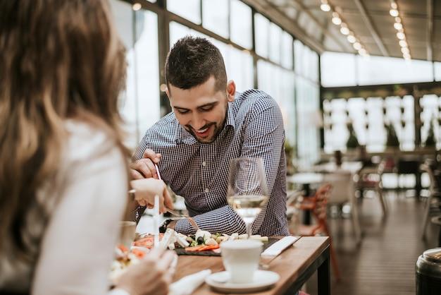Gut aussehender mann im restaurant mit dem freundessen.