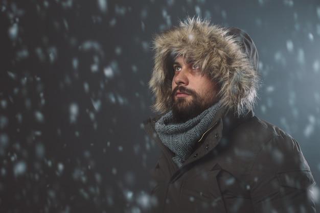 Gut aussehender mann im schneesturm