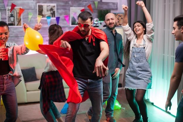 Gut aussehender mann im superhelden-kostüm tanzt auf disco-musik auf der party von freunden.