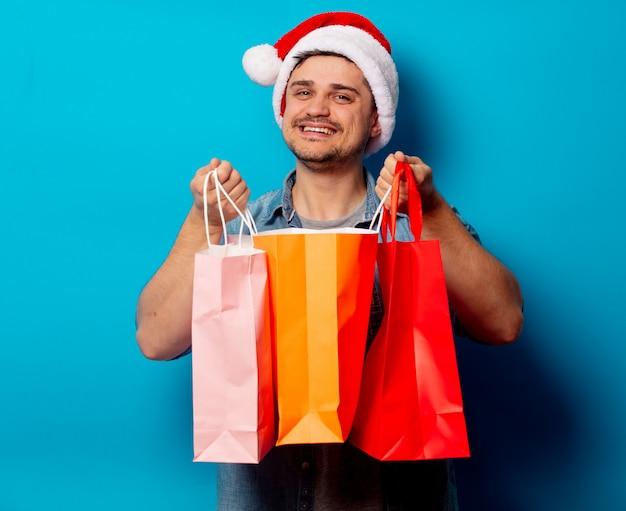 Gut aussehender mann im weihnachtshut mit einkaufstaschen
