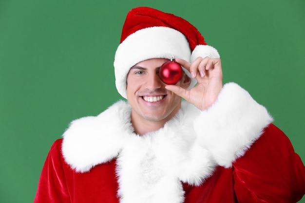 Gut aussehender mann im weihnachtsmann-kostüm, der glänzende kugel auf heller oberfläche hält