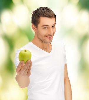Gut aussehender mann im weißen hemd mit grünem apfel