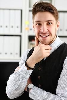 Gut aussehender mann in anzug und krawatte steht im büro