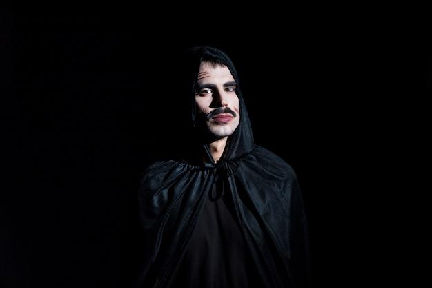 Gut aussehender mann in cape mit kapuze