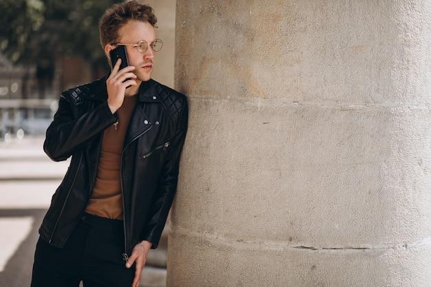 Gut aussehender mann in den schauspielen unter verwendung des telefons