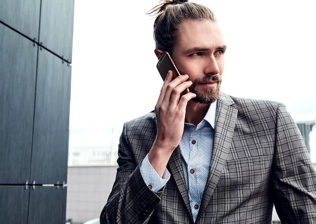 Gut aussehender mann in der grauen karierten klage, die mit smartphone spricht