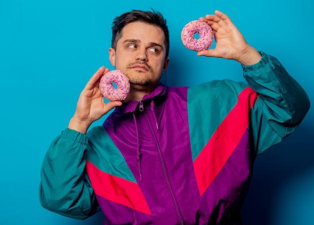 Gut aussehender mann in der jacke der 90er jahre mit donnut