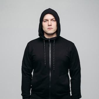 Gut aussehender mann in der schwarzen hoodieaufstellung