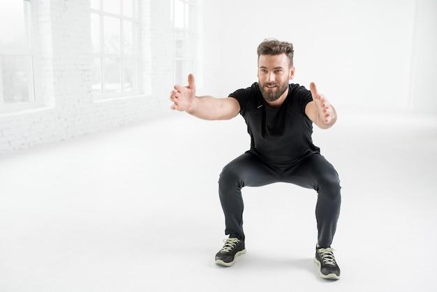 Gut aussehender mann in der schwarzen sportbekleidung, der planke im weißen turnhalleninnenraum hält