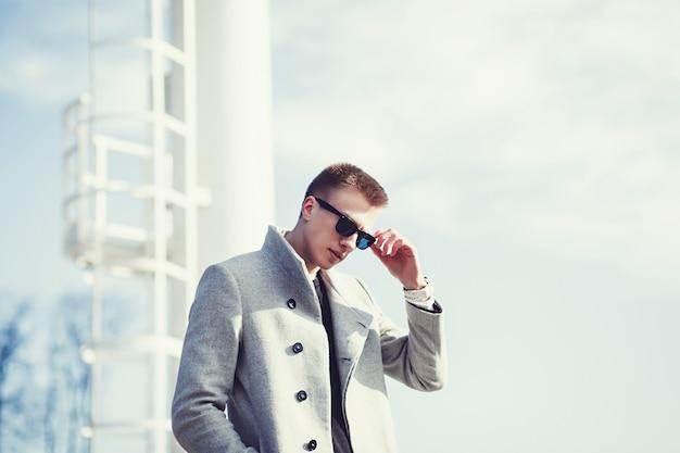 Gut aussehender mann in der sonnenbrille und im herbstmantel
