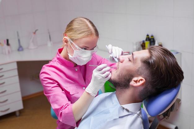 Gut aussehender mann in der zahnarztpraxis