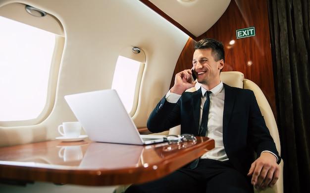 Gut aussehender mann in einem anzug lächelt und schaut durch das fenster, während er telefoniert, business class mit einem laptop und einer tasse kaffee fliegt.