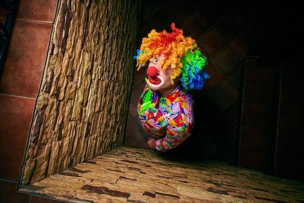 Gut aussehender mann in einem clownkostüm schaut oben