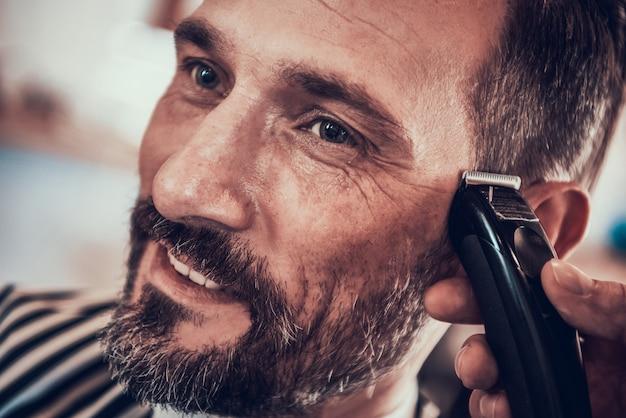 Gut aussehender mann in einem glatten haarschnitt des friseursalons